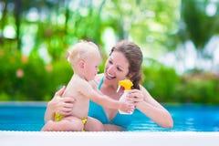 Mime a aplicar la pantalla de sol en bebé en piscina Fotos de archivo
