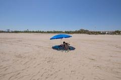 Mime a aplicar la protección solar en niño debajo del paraguas en la playa Imagenes de archivo