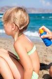 Mime a aplicar la protección solar a su niño en una playa Fotografía de archivo libre de regalías