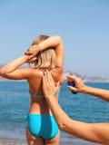 Mime a aplicar la protección solar a su niño en una playa Imagenes de archivo