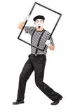 Mime artist holding a big picture frame Stock Photography