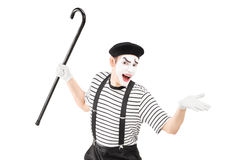 Mime artist holding a cane and gesturing. Isolated on white background Stock Photo