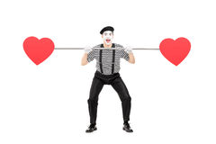 Mime artist holding a pipe with hearts on both ends Royalty Free Stock Photo