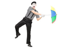 Mime artist holding an umbrella simulating being blown by wind Royalty Free Stock Images