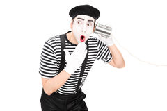 Mime artist listening through a tin can phone. Surprised mime artist listening through a tin can phone isolated on white background Royalty Free Stock Photo