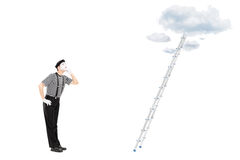 Mime artist looking up with ladder in front of him Royalty Free Stock Image