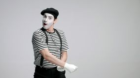 Mime artist pulling an invisible rope. Isolated on gray background stock footage