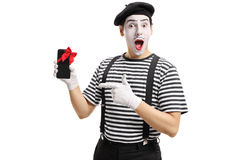 Mime artist showing phone wrapped with red ribbon and pointing Royalty Free Stock Images