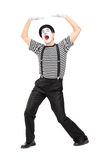 Mime artist simulate carrying something over head. Mime artist simulate carrying something over his head isolated on white background Stock Photography