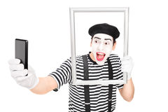 Mime artist taking selfie behind a picture frame Royalty Free Stock Photos