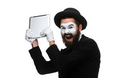 Mime as a businessman throws computer in rage stock images