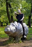 The mime astride a rhinoceros. Listens to radio Stock Image