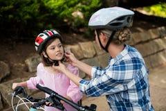 Mime a ayudar a la hija en casco de la bicicleta que lleva en parque Imágenes de archivo libres de regalías