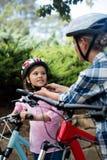 Mime a ayudar a la hija en casco de la bicicleta que lleva en parque Foto de archivo libre de regalías