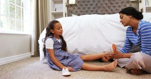 Mime a ayudar a su hija llevar los zapatos en el dormitorio 4k almacen de video