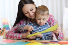 Mime a ayudar a su niño cortar el papel coloreado fotografía de archivo libre de regalías