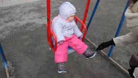 Mime a balancear en el oscilación a su niño feliz de 1 año en el patio Primavera