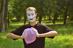 Mime and balloon. The guy the mime compresses a balloon Stock Image