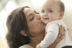 Madre que besa al bebé Fotos de archivo libres de regalías