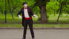 Mime catches his colleague with invisible lasso in the park stock video footage