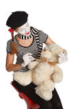 Mime comedian playing with teddy bear Stock Photos