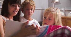 Mime con el libro de lectura de los niños en cama junto metrajes