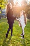 Mime con la hija siete años en parque del otoño en la puesta del sol Fotos de archivo libres de regalías