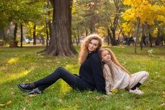 Mime con la hija siete años en parque del otoño en la puesta del sol Imagenes de archivo