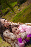 Mime con la ropa de la piel de la hija que lleva que sienta al aire libre el abarcamiento y que sonríe, fondo verde de la natural Fotos de archivo