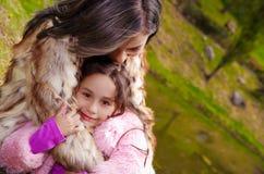 Mime con la ropa de la piel de la hija que lleva que sienta al aire libre el abarcamiento y que sonríe, fondo verde de la natural Imágenes de archivo libres de regalías