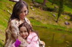 Mime con la ropa de la piel de la hija que lleva que sienta al aire libre el abarcamiento y que sonríe, fondo verde de la natural Foto de archivo libre de regalías