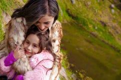 Mime con la ropa de la piel de la hija que lleva que sienta al aire libre el abarcamiento y que sonríe, fondo verde de la natural Foto de archivo