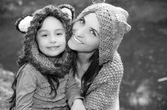 Mime con las sudaderas con capucha que llevan de la hija y la ropa caliente que sientan al aire libre el abarcamiento feliz, fond Fotografía de archivo