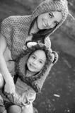 Mime con las sudaderas con capucha que llevan de la hija y la ropa caliente que sientan al aire libre el abarcamiento feliz, fond Imagenes de archivo