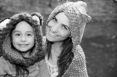 Mime con las sudaderas con capucha que llevan de la hija y la ropa caliente que sientan al aire libre el abarcamiento feliz, fond Foto de archivo libre de regalías