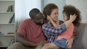 Mime a cosquillear y a divertir a su pequeña hija, familia que se sienta en el sofá almacen de video