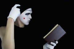 Mime da leitura com o livro em um fundo preto Imagem de Stock
