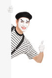 Mime dancer giving a thumb up behind a white panel. Isolated on white background Stock Images