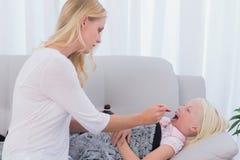 Mime a darle la medicina de la hija en una cuchara Imagen de archivo