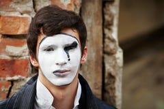 Mime del individuo contra una pared de ladrillo vieja. Imagen de archivo libre de regalías