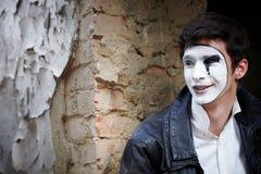 Mime del individuo contra una pared de ladrillo vieja. Fotografía de archivo libre de regalías