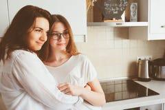 Mime a desayunar con la hija adolescente en casa en cocina blanca moderna Imagen de archivo