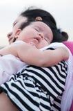 Mime a detener a su bebé recién nacido en vestido sexy mientras que ella dormía El bebé está durmiendo en su hombro de la madre e Imagenes de archivo