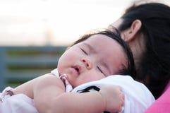 Mime a detener a su bebé recién nacido en vestido sexy mientras que ella dormía El bebé está durmiendo en su hombro de la madre e Foto de archivo