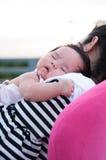 Mime a detener a su bebé recién nacido en vestido sexy mientras que ella dormía El bebé está durmiendo en su hombro de la madre e Imagen de archivo