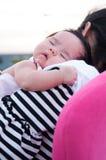 Mime a detener a su bebé recién nacido en vestido sexy mientras que ella dormía El bebé está durmiendo en su hombro de la madre e Imagen de archivo libre de regalías