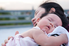 Mime a detener a su bebé recién nacido en vestido sexy mientras que ella dormía El bebé está durmiendo en su hombro de la madre e Fotos de archivo
