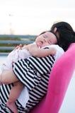 Mime a detener a su bebé recién nacido en vestido sexy mientras que ella dormía El bebé está durmiendo en su hombro de la madre e Imágenes de archivo libres de regalías