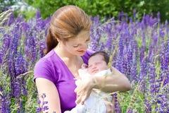 Mime a detener a su bebé recién nacido en campo de flor Imagenes de archivo