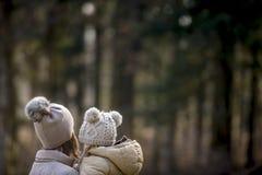 Mime a detener a su niño ambos los sombreros calientes que llevan afuera en delanteras Imagen de archivo